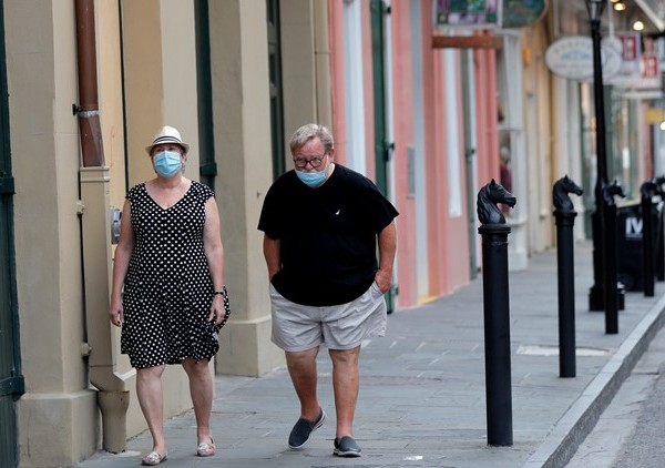 A couple walks past shuttered businesses impacted by the coronavirus epidemic, on Royal St, in the French Quarter of New Orleans, Tuesday, May 12, 2020. Attempts to curb the spread of COVID-19 have visited a kind of triple economic whammy on the state. As oil prices have plummeted, the industry laid off workers. Tourism has dried up, meaning more lost jobs. And one major tourist draw — cuisine built around fin fish, shrimp, oyster and crabs — is also suffering. (AP Photo/Gerald Herbert)