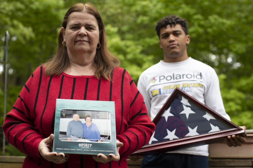 In this Friday, May 22, 2020, photo Florence Hopp, left, holds a photograph of herself and her husband Robert Hopp during a cruise in 2017, as her son J.J. Brania-Hopp holds the American flag the military presented to them after his father's death at their home in Boonton, N.J. Hopp was one of at least 79 residents of a veterans home in Paramus, New Jersey, to die from COVID-19, making the state-run facility one of the nation's worst hot spots for the virus. (AP Photo/Mary Altaffer)