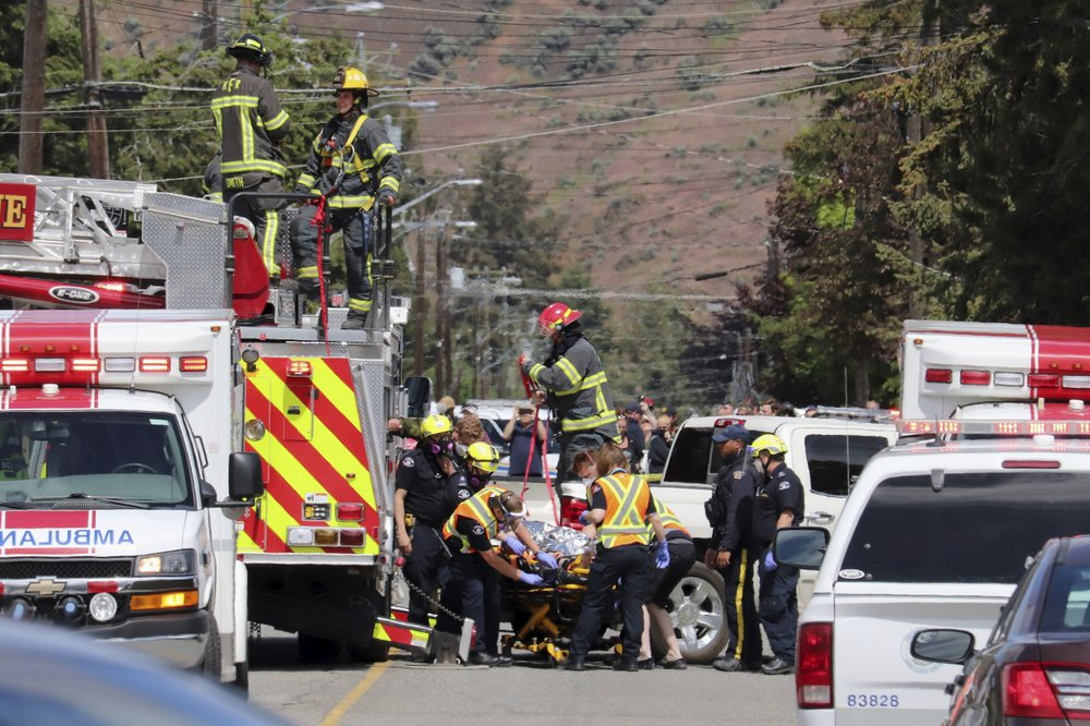 First responders transport an injured person on a stretcher at the scene of a crash involving a Canadian Forces Snowbirds aircraft in Kamloops, British Columbia, Sunday, May 17, 2020. (Brendan Kergin/Castanet Kamloops/The Canadian Press via AP)