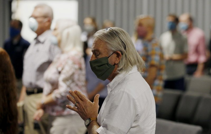 Pastor Denny Pagel prays during a service at Grace Bible Church on Sunday, May 24, 2020, in Tempe, Ariz. Parishioners practiced social distancing as the church held its first in-person service since March. (AP Photo/Ross D. Franklin)