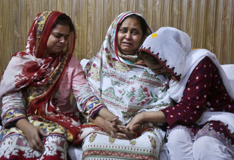 Family members of an air hostess Anam Maqsood, who was killed in Friday's plane crash, mourn for her death at their home in Lahore, Pakistan, Saturday, May 23, 2020. An aviation official says a passenger plane belonging to state-run Pakistan International Airlines carrying passengers and crew has crashed near the southern port city of Karachi. (AP Photo/K.M. Chaudary)