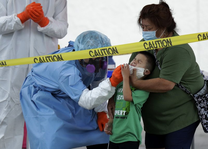 FILE - In this May 14, 2020, file photo, Jerry A Mann, center, is held by his grandmother, Sylvia Rubio, as he is tested for COVID-19 by the San Antonio Fire Department at a free walk-up test site in San Antonio. Public health officials have said robust testing for the coronavirus is essential to safely lifting stay-at-home orders and business closures, but states are creating confusion in the way they are reporting the data. (AP Photo/Eric Gay, File)
