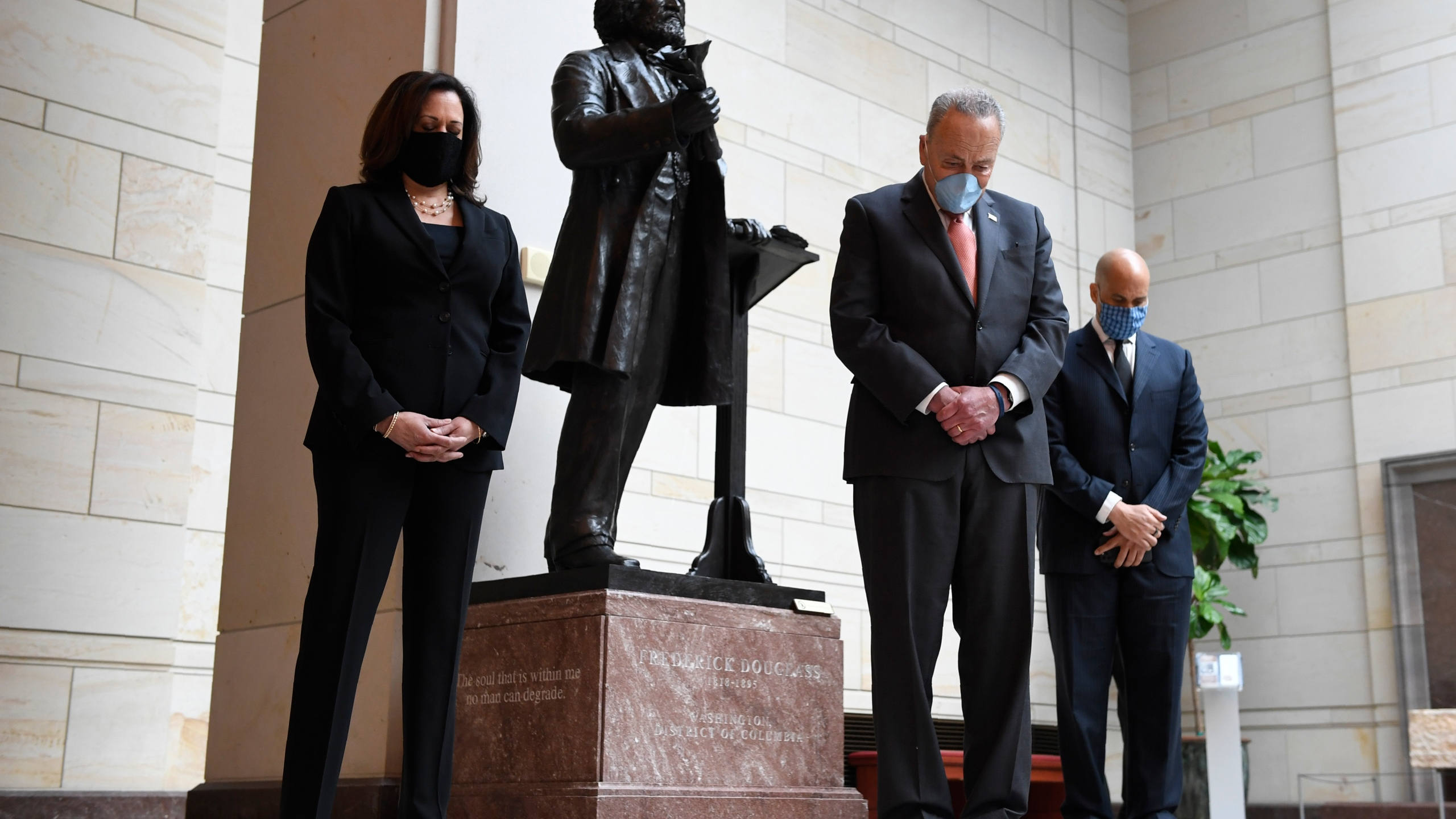 Standing near a statue of Frederick Douglass, Sen. Kamala Harris, D-Calif., left, Senate Minority Leader Sen. Chuck Schumer of N.Y., center, and Sen. Cory Booker, D-N.J.,, right, pause during a prayer Capitol Hill in Washington, Thursday, June 4, 2020, during an event to commemorate the life of George Floyd, who died after being restrained by Minneapolis police officers. (AP Photo/Susan Walsh)