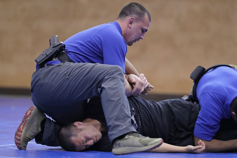 In this June 4, 2020, photo, Brandon Wilson, upper left, an instructor at the Washington state Criminal Justice Training Commission facility in Burien, Wash., restrains fellow instructor Ben Jia, lower left, during a demonstration for The Associated Press on takedown and restraint techniques taught to law enforcement officers as part of the more than 700 hours of training police and other officers are required to to through in the state. Police training has been under scrutiny again since the death of George Floyd, a black man who died after being restrained by Minneapolis police officers. (AP Photo/Ted S. Warren)