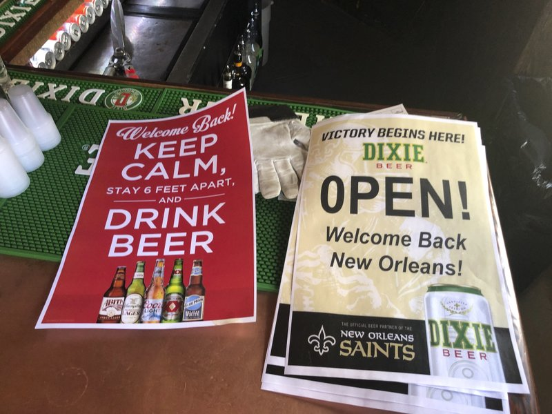 In this Friday, June 12, 2020 photo, stacks of signs for welcoming back patrons sit on the bar at Lafitte's Blacksmith Shop Bar on Bourbon Street in New Orleans. The city is allowing bars to open – with limited capacity and without live music – on Saturday. Bars were among the businesses shut down in mid-March as coronavirus infections increased in New Orleans and Louisiana became a hot spot for the disease. (AP Photo/Kevin McGill)