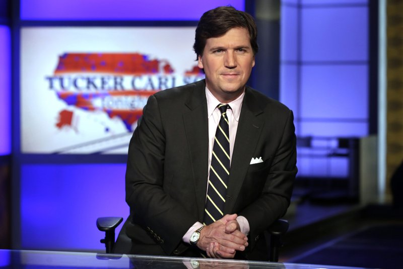 """FILE - In this March 2, 2017 file photo, Tucker Carlson, host of """"Tucker Carlson Tonight,"""" poses for photos in a Fox News Channel studio, in New York. Tucker Carlson's top writer has resigned from Fox News after secretly posting racists and sexist remarks online. CNN reported Friday, July 10, 2020 that writer Blake Neff used a pseudonym to write bigoted comments about Black and Asian people, as well as women, on the online platform AutoAdmit.(AP Photo/Richard Drew, File)"""