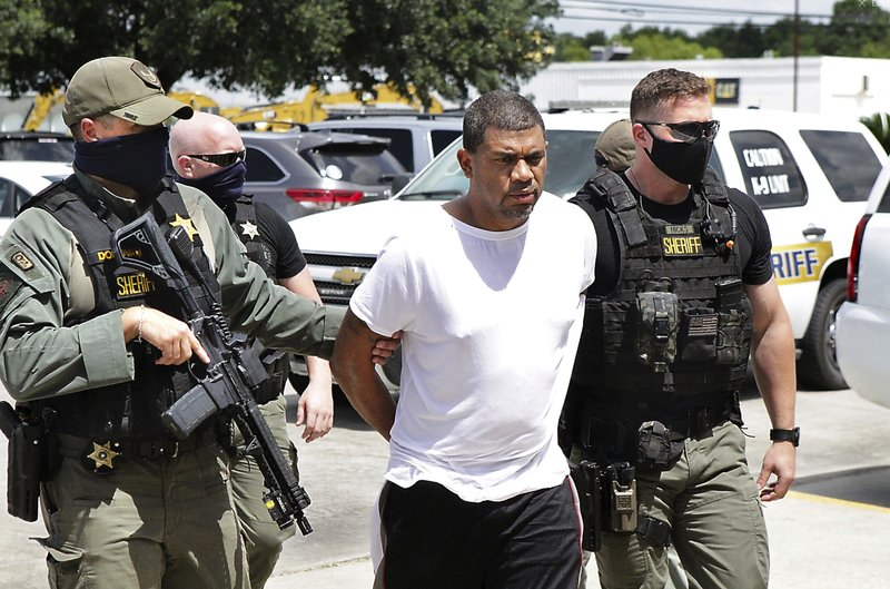 Neil Broussard, escorted by law enforcement, is brought into the Calcasieu Parish Sheriff's Office Thursday morning, July 16, 2020, in Lake Charles, La. Workers at a Dollar General store recognized Broussard, a convicted sex offender accused of killing two teenagers and kidnapping a third, and locked him in after quietly escorting other customers out. (Donna Price/The Daily Advertiser via AP)/American Press via AP)
