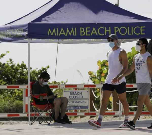 People wearing protective face masks walk past a closed entrance to the beach during the new coronavirus pandemic, Friday, July 3, 2020, in the South Beach neighborhood of Miami Beach, Fla. Beaches throughout South Florida are closed for the busy Fourth of July weekend to avoid further spread of the new coronavirus. (AP Photo/Lynne Sladky)