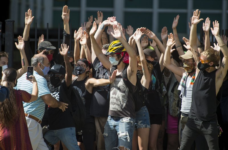 New Orleans Renters Rights Assembly protesters hold their hands in the air as they block people, left, from entering First City Court near New Orleans City Hall on Thursday, July 30, 2020 (Chris Granger/The Advocate via AP)