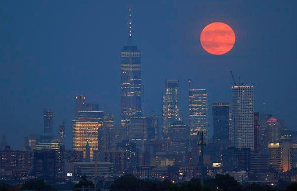 On the 50th anniversary of the launch of Apollo 11, the full buck moon rises above the skyline of lower Manhattan and One World Trade Center in New York City on July 16, 2019 as seen from Kearney, New Jersey.