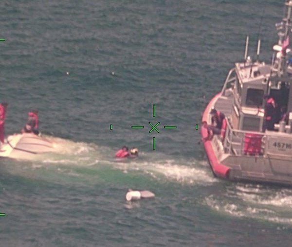 In this photo released by the U.S. Coast Guard, members of the Coast Guard rescue a family of four, Wednesday, Aug. 5, 2020, from a vessel taking on water 17 miles south of Southwest Pass near Venice, La. (U.S. Coast Guard via AP)