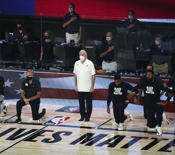 San Antonio Spurs head coach Gregg Popovich, standing at center, wears a mask while players kneel before an NBA basketball game against the Houston Rockets, Tuesday, Aug. 11, 2020, in Lake Buena Vista, Fla. (Kim Klement/Pool Photo via AP)