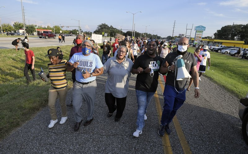 Marja Broussard, center, president of the Lafayette chapter of the NAACP, walks down Evangline Thruway with others demanding justice for Trayford Pellerin, Saturday, Aug. 22, 2020, in Lafayette, La. Pellerin was shot and killed by Lafayette police officers while armed with a knife the night before. (Brad Kemp/The Advocate via AP)