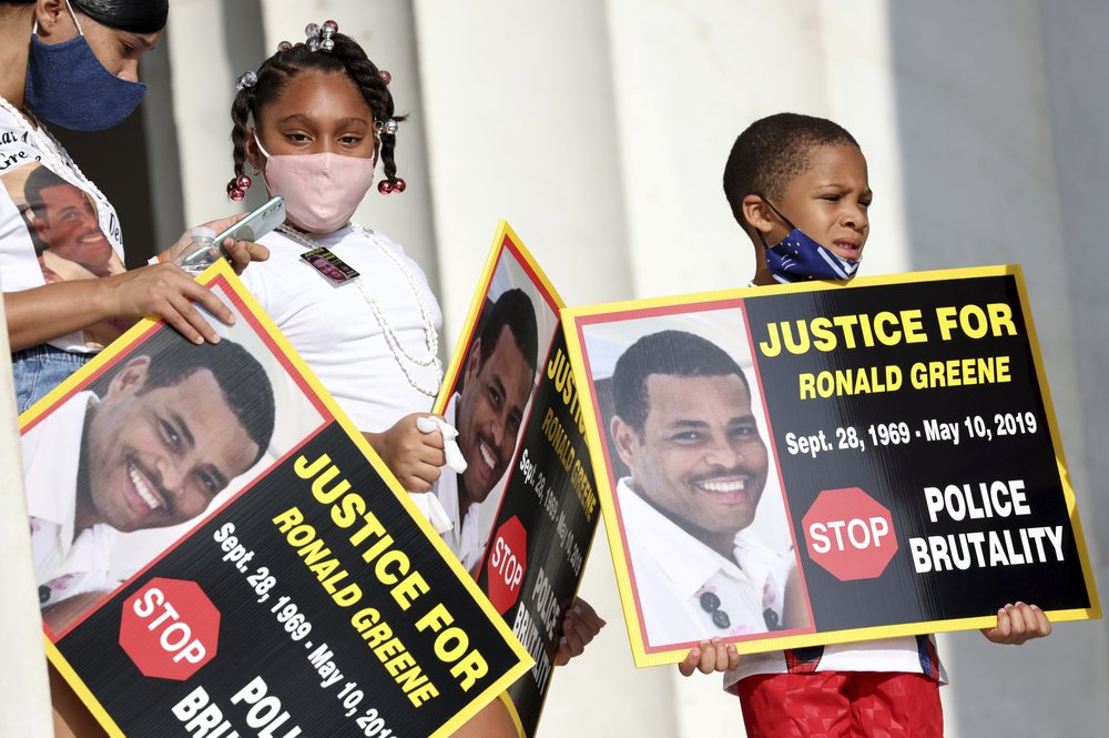 "FILE - In this Aug. 28, 2020 file photo, family members of Ronald Greene listen to speakers as demonstrators gather for the March on Washington, in Washington, on the 57th anniversary of the Rev. Martin Luther King Jr.'s ""I Have A Dream"" speech. Officials told The Associated Press, federal authorities are investigating the death of Greene during what Louisiana State Police described as a struggle to take him into custody following a rural police chase last year. The death of the 49-year-old remains shrouded in secrecy because State Police have declined to release body-camera footage related to the May 2019 chase north of Monroe, La. (Michael M. Santiago/Pool via AP)"