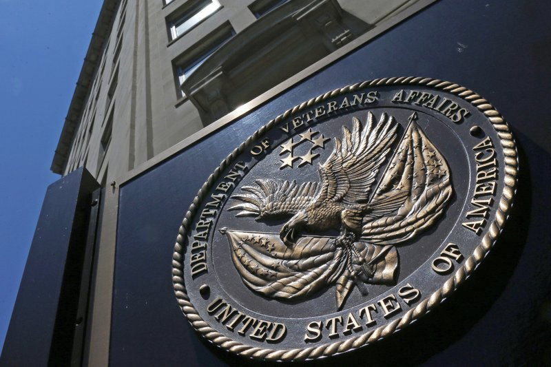 """FILE - This June 21, 2013, file photo, shows the seal affixed to the front of the Department of Veterans Affairs building in Washington. In a federal lawsuit filed this week, U.S. Navy veteran from South Carolina says he ended up with """"full-blown AIDS,"""" because government health care workers never informed him of his positive test result in 1995. He says the test was done as part of standard lab tests at a U.S. Department of Veterans Affairs medical center in Columbia, South Carolina. A V.A. spokeswoman says the agency typically does not comment on pending litigation. (AP Photo/Charles Dharapak, File)"""