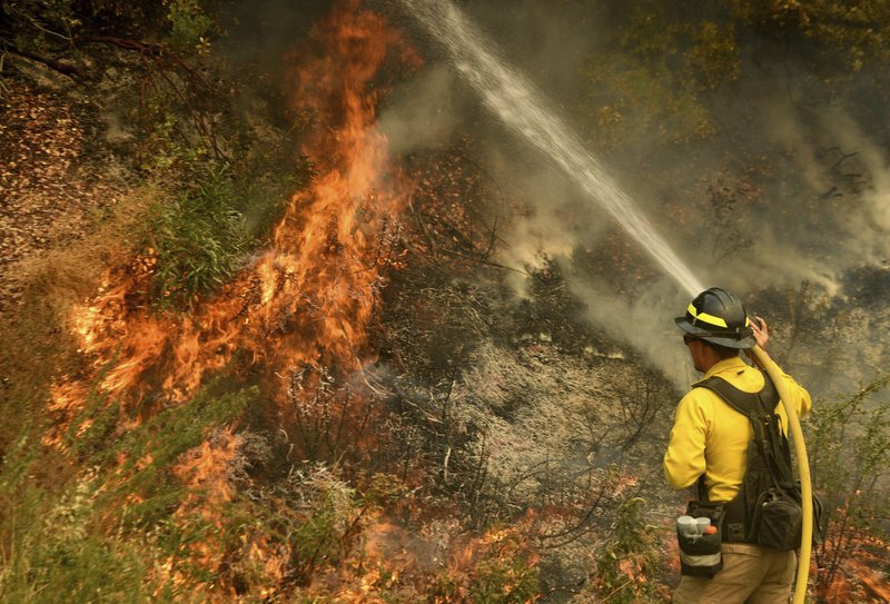 A firefighter puts out a hot spot along Highway 38 northwest of Forrest Falls, Calif., as the El Dorado Fire continues to burn Thursday afternoon, Sept. 10, 2020. The fire started by a device at a gender reveal party on Saturday. (Will Lester/The Orange County Register/SCNG via AP)