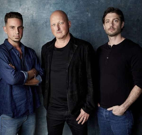 """FILE - James Safechuck, from right, director Dan Reed and Wade Robson pose for a portrait to promote the film """"Leaving Neverland"""" during the Sundance Film Festival on Jan. 24, 2019, in Park City, Utah. A Los Angeles judge has dismissed the lawsuit of one of two men who alleged that Michael Jackson abused them as boys in the documentary """"Leaving Neverland."""" Judge Mark Young ruled on Tuesday, Oct. 20, 2020, that 42-year-old Safechuck couldn't sue the two corporations Jackson owned that are named as defendants. The similar lawsuit of fellow accuser Robson, which was also revived by the appeals court, remains alive. (Photo by Taylor Jewell/Invision/AP, File)"""