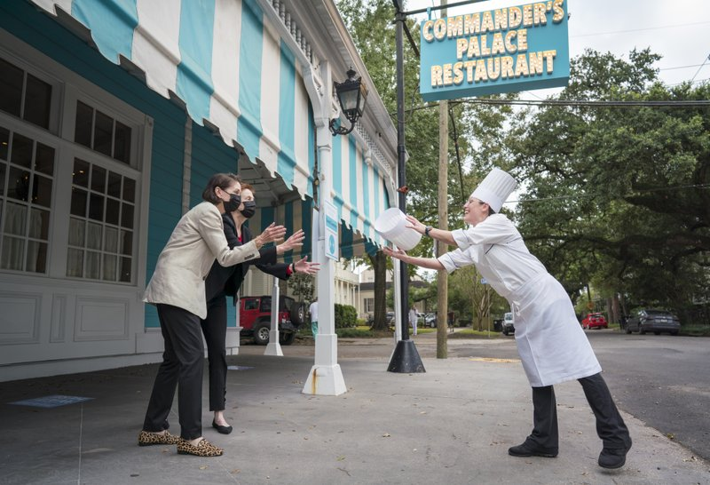 Commander's Palace proprietors Lally Brennan and Ti Martin, left, toss the chef's toque to Meg Bickford outside the restaurant, Thursday, Sept. 24, 2020, in New Orleans. Bickford will be the first female executive chef in the storied history of the restaurant. (Chris Granger/The Advocate via AP)