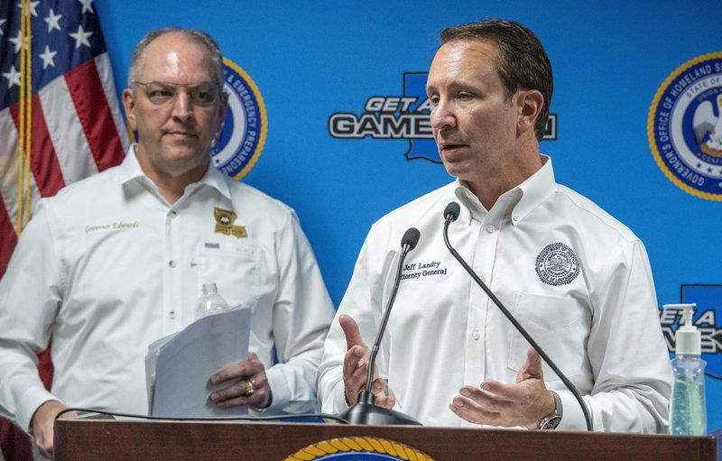 Attorney General Jeff Landry, right, speaks about medicines being donated by drug companies to help the fight against the coronavirus during a press conference during a press conference at the Governor's Office of Homeland Security & Emergency Management, Monday April 6, 2020, in Baton Rouge, La. Louisiana Gov. John Bel Edwards listens at left. (Bill Feig/The Advocate via AP, Pool)