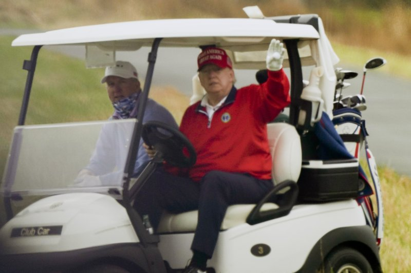 President Donald Trump waves from a golf cart as he plays golf at Trump National Golf Club, Friday, Nov. 27, 2020, in Sterling, Va. (AP Photo/Alex Brandon)