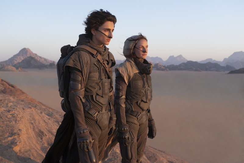 "This image released by Warner Bros. Entertainment shows Timothee Chalamet, left, and Rebecca Ferguson in a scene from the upcoming 2021 film ""Dune."" Warner Bos. Pictures on Thursday announced that all of its 2021 film slate will stream on HBO Max at the same time they play in theaters. (Chia Bella James/Warner Bros. Entertainment via AP)"