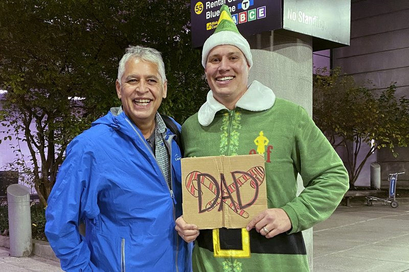 "Doug Henning, right, who was adopted as a baby, poses with his biological father after meeting face to face for the first time on Tuesday, Nov. 24, 2020, at Logan International Airport in Boston. Henning, of Eliot, Maine, wore a costume like the one actor Will Ferrell's character wore in the movie ""Elf"" and he broke into the same awkward song from the movie while meeting his father. (Rebecca Taylor Henning via AP)"