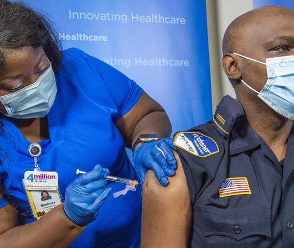 Lt. Ollie Martin, right, with Ochsner Security, is inoculated with the Pfizer-BioNTech COVID-19 vaccine by nurse Meshoca Williams at Ochsner Hospital on O'Neal Lane, Tuesday, Dec. 15, 2020, in Baton Rouge, La. (Bill Feig/The Advocate via AP, Pool)