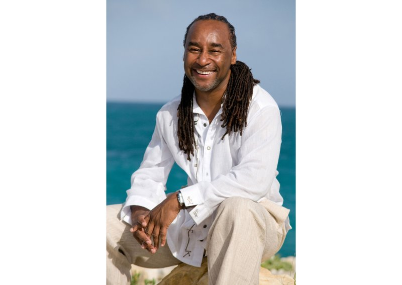 """This undated image released by Joseph Jones shows author Eric Jerome Dickey in Antigua. Dickey, the bestselling novelist who blended crime, romance and eroticism in """"Sister, Sister,"""" """"Waking With Enemies"""" and dozens of other stories about contemporary Black life, has died at age 59. Dickey's publicist at Penguin Random House, Emily Canders, told The Associated Press that the author died Sunday, Jan. 3, 2021 in Los Angeles after a long illness. (Joseph Jones via AP)"""
