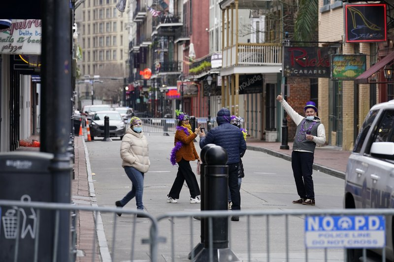 Tourists from Brooklyn take photos on a nearly deserted Bourbon Street during Mardi Gras in the French Quarter of New Orleans, Tuesday, Feb. 16, 2021. (AP Photo/Gerald Herbert)