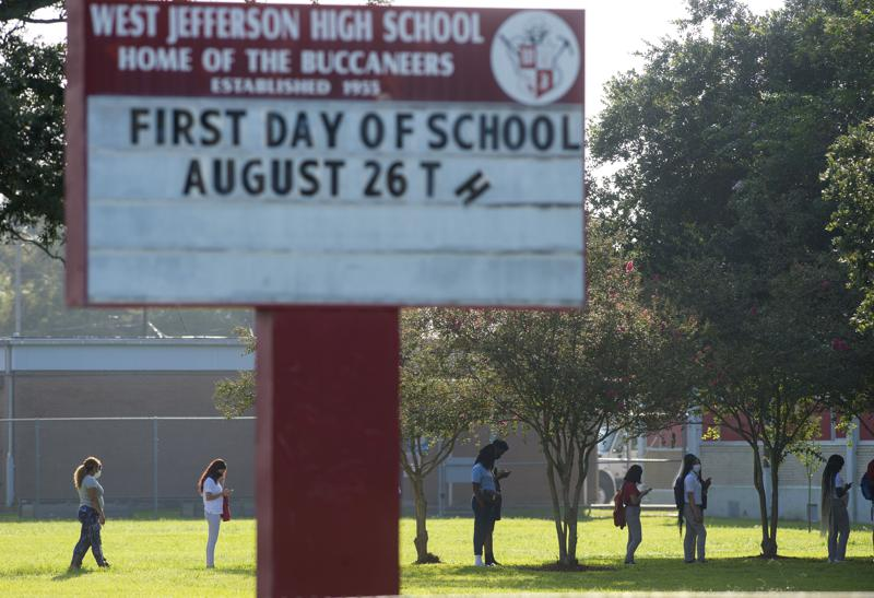 FILE - In this Aug. 31, 2020 file photo, students returning to West Jefferson High School in Harvey, La., keep a distance from each other as they walk into school for in-class learning during the COVID-19 pandemic. Louisiana lawmakers intend to give K-12 public school teachers a $1,000 raise next year, more than double the amount proposed by Gov. John Bel Edwards. That's according to the leader of the Senate Education Committee, who announced the move Thursday, April 29, 2021.(Chris Granger/The Advocate via AP)