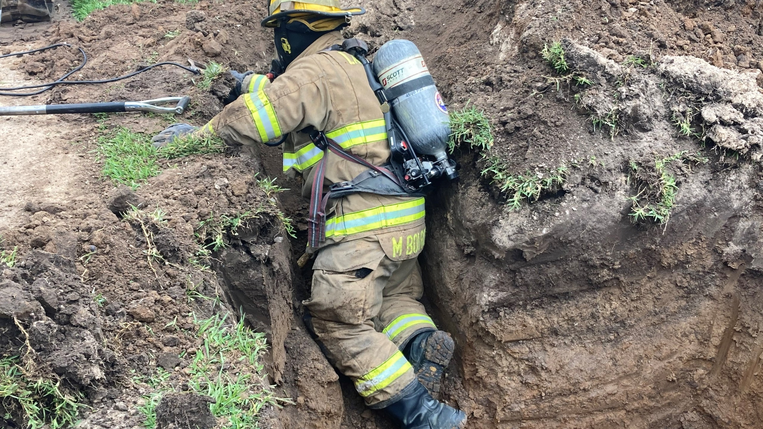 Firefighter in hole placing a temporary patch on the gas leak. (Alton Trahan, Lafayette Fire Department)
