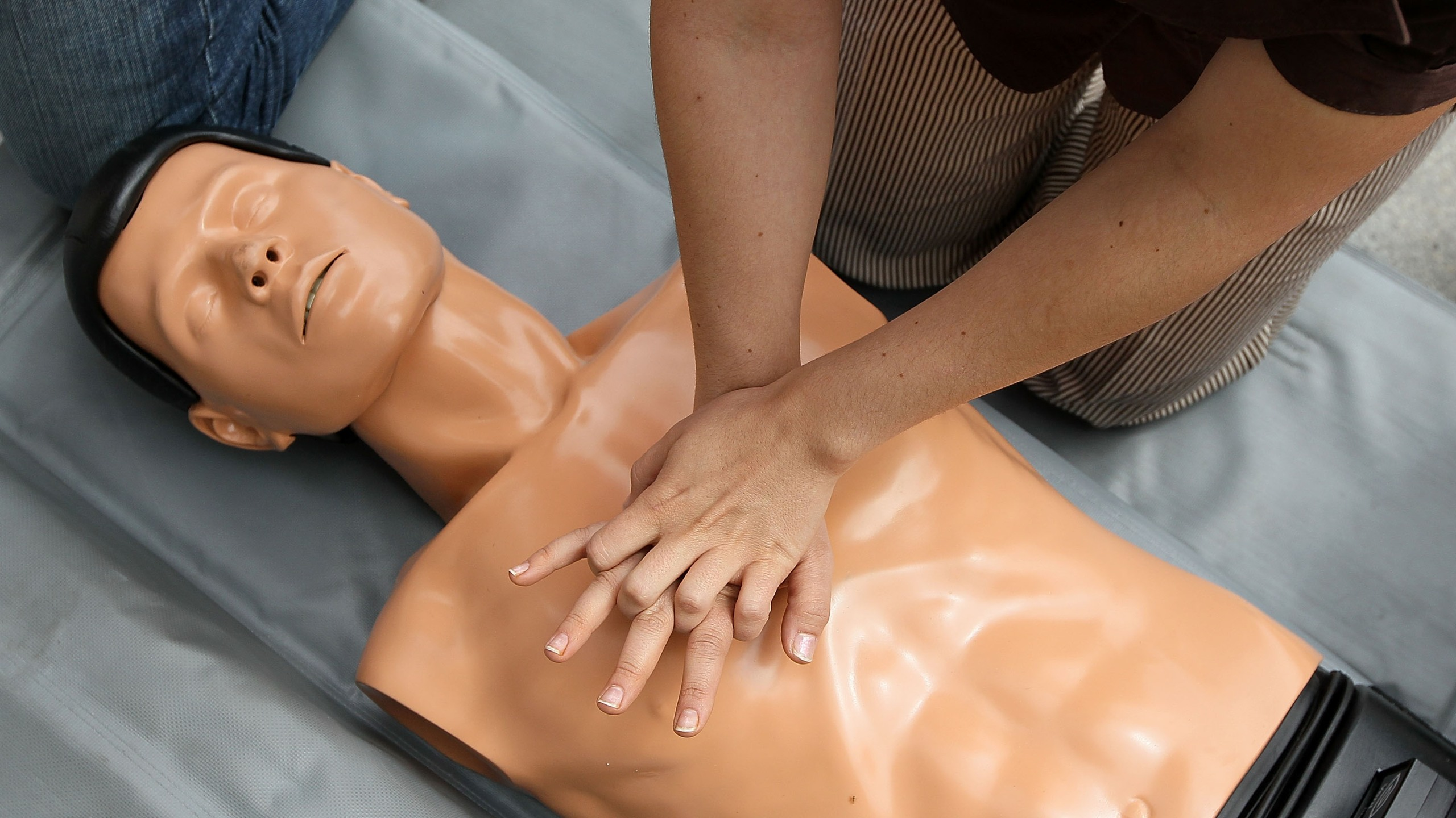 SAN FRANCISCO - JUNE 01: A woman performs chest compressions on a mannequin while learning C.P.R. on the steps of San Francisco city hall following a press conference celebrating the 50th anniversary of lifesaving by using C.P.R. June 1, 2010 in San Francisco, California. Dozens of people stopped for free C.P.R. lessons given by volunteers from the San Francisco Paramedic Association. C.P.R. (cardiopulmonary resuscitation) is a combination of rescue breathing and chest compressions delivered to aid victims who are in cardiac arrest by keeping oxegenated blood flowing to vital organs. (Photo by Justin Sullivan/Getty Images)