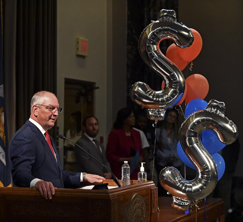 """Gov. John Bel Edwards stands near balloons in the shape of dollar signs during a news conference at the Louisiana State Capitol in Baton Rouge, La., on Thursday, June 17, 2021, to announce $2.3 million in cash prizes and scholarships during the """"Shot at a Million"""" campaign to get residents of the state of Louisiana vaccinated against the coronavirus. (Hilary Scheinuk/The Advocate via AP)"""