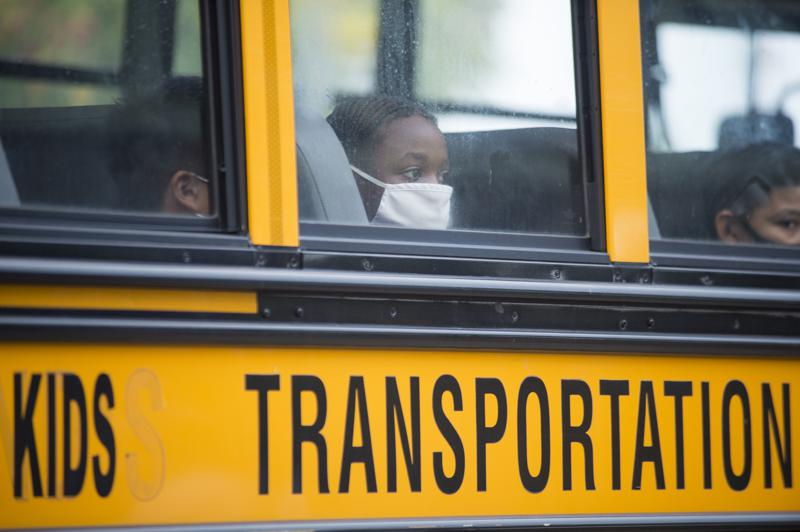 FILE - In this Oct. 12, 2020, file photo, students arrive by bus at Foundation Preparatory School for their return to school during the coronavirus in New Orleans. It was the first day of in-person learning for fifth-12th grade public school students in Orleans Parish. Despite climbing numbers of COVID-19 cases around Louisiana, state education leaders are leaving decisions on mask mandates, physical distancing and other measures aimed at lessening coronavirus spread to local public school districts for the upcoming year. (Chris Granger/The Times-Picayune/The New Orleans Advocate via AP, File)