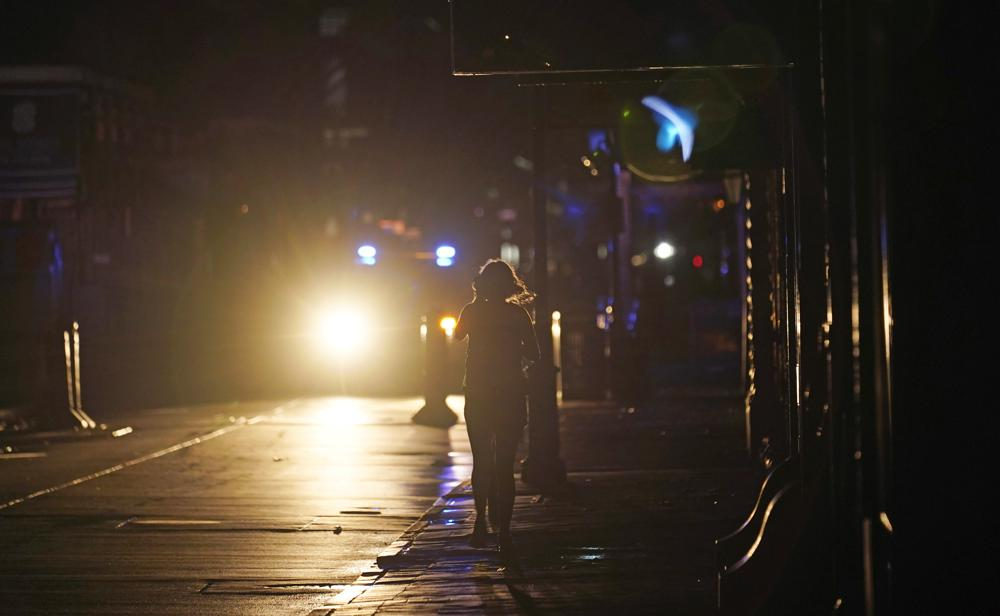 A police officer patrols past woman walking along Bourbon Street in the French Quarter after Hurricane Ida knocked out power to the city, Monday, Aug. 30, 2021, in New Orleans, La. (AP Photo/Eric Gay)