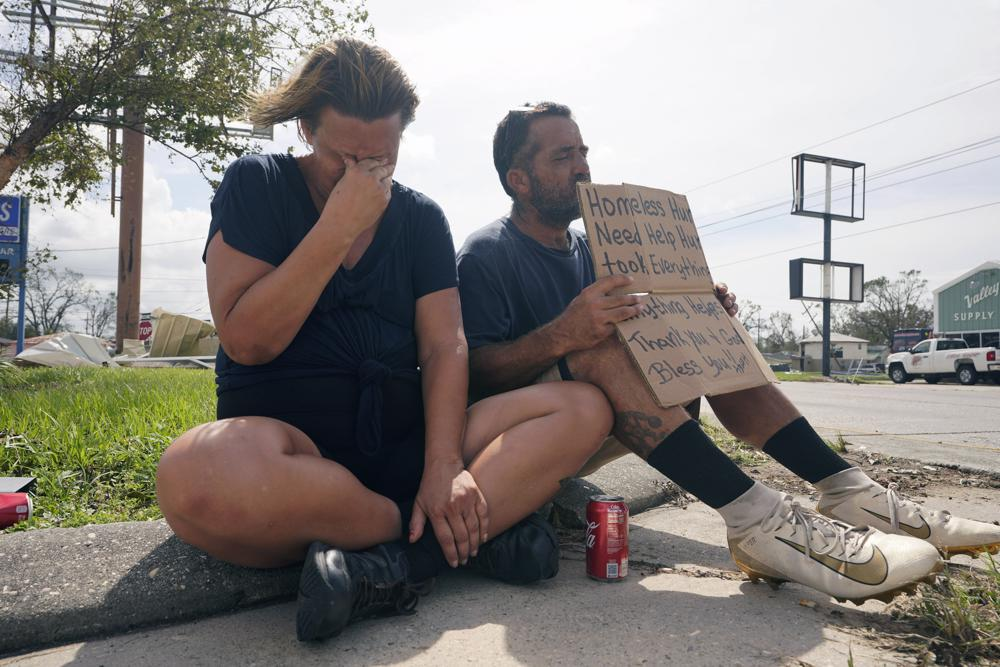 Homeless couple Angelique Hebert, and husband Wilfred Hebert, ask for help on a sidewalk as they try to recover from the effects of Hurricane Ida Tuesday, Aug. 31, 2021, in Houma, La. (AP Photo/Steve Helber)