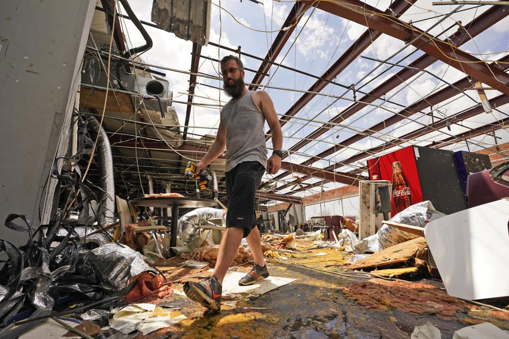 Jason Ledet relieves a tool as he works in a destroyed bowling alley as they try to recover from the effects of Hurricane Ida Tuesday, Aug. 31, 2021, in Houma, La. (AP Photo/Steve Helber)